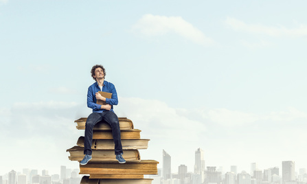 Guy sitting on pile of books with one in hands